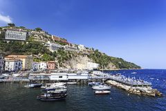 Marina Grande in Sorrento, Italy, Campania region on a beautiful. Boats and buildings along the cliffs at Marina Grande in Sorrento, Italy, Campania region on a royalty free stock image