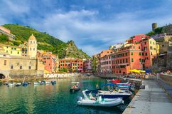 Marina harbor with boats and yachts, promenade, Chiesa di Santa Margherita church, green hill and colorful buildings houses in Ver royalty free stock image