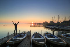 Marina joy. Man standing on a jetty in a marina during a foggy sunrise at a lake Stock Photography