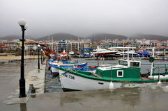 The marina, many different boats, view on mountains and waterfront, fog Stock Image