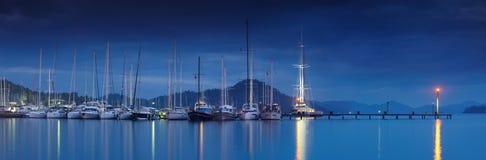 Marina på natten med förtöjde yachter Royaltyfria Bilder