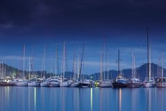 Marina på natten med förtöjde yachter Arkivbild