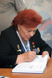 Marina Popovich gives autographs at MAKS-2013. A pilot Marina Popovich gives autographs at International Aerospace Salon MAKS-2013. She signs her book I am a Royalty Free Stock Image