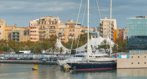 Marina Port Vell near Shopping centre in Barcenlona, Spain. Large yachts & sailboat moored at waterfront spaces. & Condos with a view in afternoon sun in stock photography