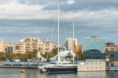 Marina Port Vell near Shopping centre in Barcenlona, Spain. Large yachts & sailboat moored at waterfront spaces. & Condos with a view in afternoon sun in stock image