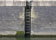 Marina quay wall and ladder. Old worn bricks stock photos