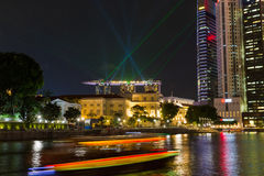 Marina Sands Bay Resort Laser Show. BOAT QUAY, SINGAPORE - JULY 29, 2016: A tourist boat passes the historic Boat Quay area as a laser light show display from Royalty Free Stock Images