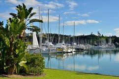 A marina scene. Yacht masts reflecting in water of a marina stock photo