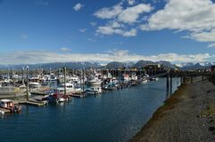 A marina with snow capped mountains in the background. Glacier snow remains year-round as fishing season is in full swing royalty free stock photography
