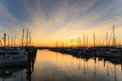Marina at sunset, masts and clouds reflected in the water. A tranquil view of a marina. An attractive golden sunset is reflected in the glassy waters. Photo royalty free stock image