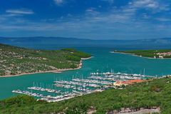 Marina in turquoise lagoon at Adriatic sea. Near olive tree plantation. Cres island, Croatia, popular touristic destination Stock Photography