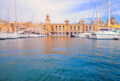 Marina in Vittoriosa, Valetta Great Harbor. Marina in Vittoriosa, one of the Three Cities across Valetta Bay, Malta; the building with the clock is Maritime Royalty Free Stock Photos