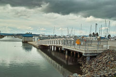 Marina walkway and dock. Under a dark, cloudy sky Royalty Free Stock Photos
