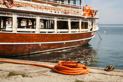 Marina with a wooden boat moored on the shore. Royalty Free Stock Photography