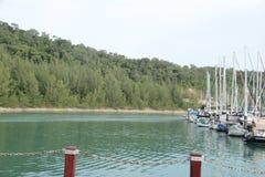 Marinabryggan med seglar fartyg nära kullebakgrund arkivbild