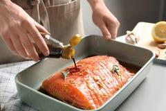 Marinade de versement de femme sur les saumons crus photo libre de droits