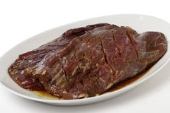 Marinaded flank steak on a plate. Two pieces of marinded flank steak resting on a plate prior to grilling royalty free stock photo