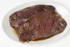 Marinaded flank steak on a plate. Two pieces of marinded flank steak resting on a plate prior to grilling stock photo