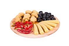 Marinaded vegetables on wooden platter. Stock Images