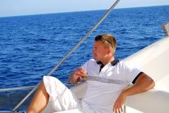 Marinaio che si distende sulla barca che beve caffè freddo Fotografia Stock