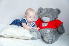 Marinaio del bambino sul cuscino con l'orsacchiotto immagini stock