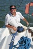 Marinaio di mezza età sulla navigazione della barca Fotografie Stock