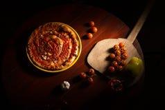 Marinara della pizza con aglio ed i pomodori sulla pagaia di legno Immagine Stock Libera da Diritti