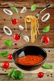 Marinara sauce with flying ingredients to prepare it Royalty Free Stock Photo