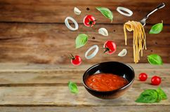 Marinara sauce with flying ingredients to prepare it Royalty Free Stock Photography
