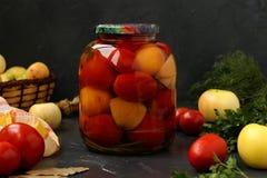 Marinated томаты в опарнике расположены на темной предпосылке стоковое изображение
