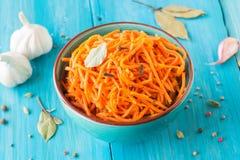 Marinated моркови в корейском стиле в керамических изделиях на деревянной голубой предпосылке стоковая фотография