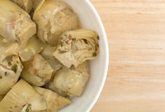 Marinated artichoke hearts in a bowl atop a table Royalty Free Stock Photos