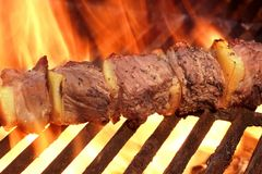 Marinated BBQ Meat Or Beef Kebab Kabob On Hot Grill. Flames of Fire on The Background. Summer Party or Picnic Food stock images