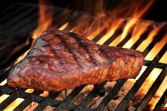 Marinated Beef Steak On The Flaming Hot BBQ Grill. Marinated Beef Steak On The Hot BBQ Charcoal Grill. Flame Of Fire In The Background royalty free stock photos