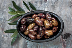 Marinated Black Olives. In small dish, with leaves, over slate stock photo