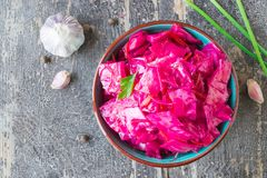 Marinated cabbage with beets on a wooden background royalty free stock photography