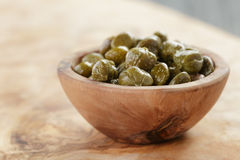 Marinated capers in bowl on olive board Royalty Free Stock Photography