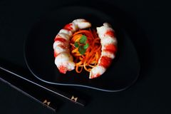 Original culinary dish of delicious pickled carrots and shrimp necks on black ceramic dish with bamboo sticks on dark background. stock image