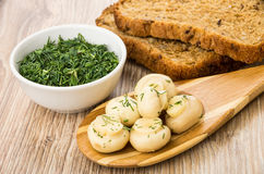 Marinated champignons with dill on bamboo spoon, dill in bowl Royalty Free Stock Photography