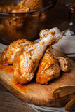 Marinated chicken drumsticks on a wooden chopping board. Royalty Free Stock Images