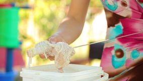 Marinated chicken is put on a skewer for grilling stock footage