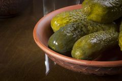Marinated cucumbers in a pottery. On a wooden table Royalty Free Stock Images