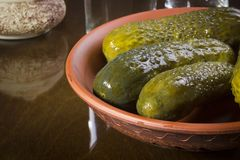 Marinated cucumbers in a pottery. On a wooden table Royalty Free Stock Image