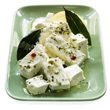 Marinated Feta Cheese with Bay Leaves. Dish of creamy marinated feta cheese with bay leaves and preserved lemon.  Isolated on white Royalty Free Stock Photo