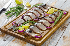 Marinated Fillets of Fresh atlantic mackerel fish cut in slices. On chopping board with rosemary, lemon, red onion and spices, knife and lemon pieces on old Stock Image