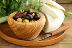Marinated green and black olives (Kalamata). In a wooden bowl Stock Images