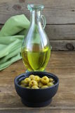 Marinated green olives and a bottle of oil Royalty Free Stock Images