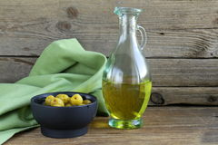 Marinated green olives and a bottle of oil. On wooden table Stock Images