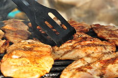 Marinated and Grilled chicken breast. Checking for the right amount of chicken breast with a big fork Stock Image