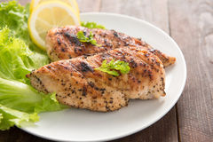 Marinated grilled chicken breasts cooked BBQ and served with fre. Sh herbs and lemon Stock Images